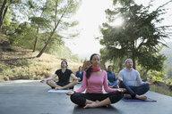 Serene people meditating in lotus position on deck - HEROF27333