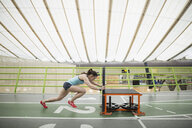 Runner pushing sprinting sled on indoor track - HEROF27378