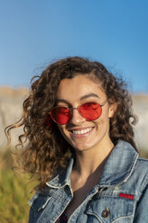 Portrait of happy young woman with curly brown hair wearing red sunglasses - AFVF02575