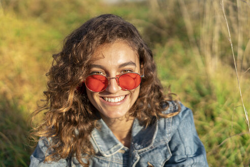Portrait of happy young woman with curly brown hair wearing red sunglasses - AFVF02578