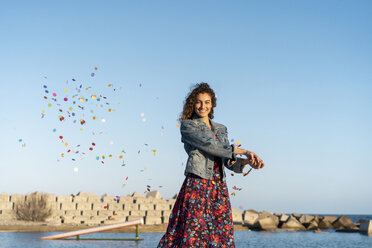 Portrait of smiling young woman throwing confetti in the air - AFVF02584