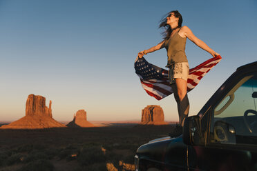 USA, Utah, Monument Valley, Woman with United States of America flag enjoying the sunset in Monument Valley - GEMF02868