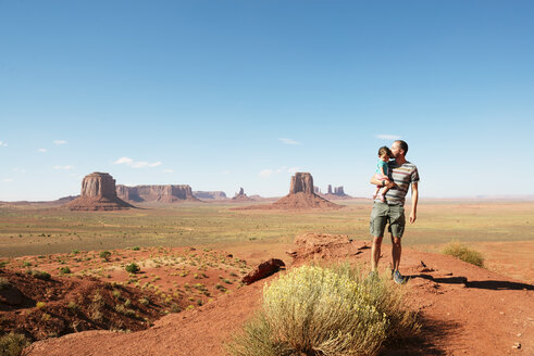 USA, Utah, Monument Valley, Father kissing his daughter on viewpoint - GEMF02880