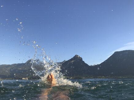 Austria, Salzburg, Salzkammergut, Salzburger Land, Wolfgangsee, St. Wolfgang, woman jumping into refreshing lake - GWF05986