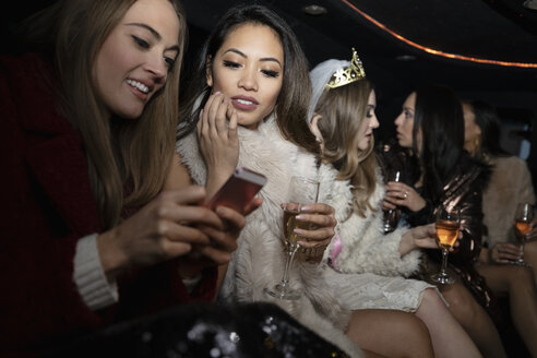 Bachelorette and friends drinking champagne in limousine - HEROF27399