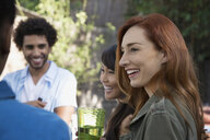 Smiling friends talking on patio - HEROF27430