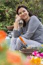 Pensive brunette woman planting flowers in backyard - HEROF27500
