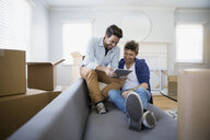 Homosexual couple using digital tablet sofa moving boxes - HEROF27575