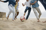 Friends playing soccer on beach - HEROF27602