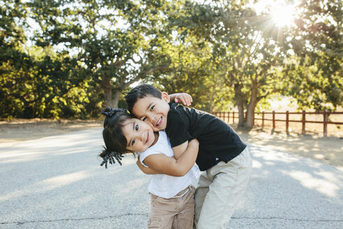 Portrait of cute siblings embracing while standing on road against trees in park - CAVF62716