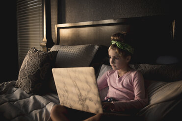 Cute girl using laptop computer while relaxing on bed at home - CAVF62731