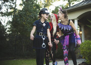 Happy friends in Halloween costumes holding hands while walking at yard - CAVF62737
