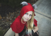 High angle portrait of girl wearing Halloween costume crouching on footpath in yard during sunset - CAVF62740