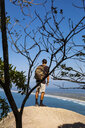 Full length of backpacker looking at sea while standing on cliff against blue sky - CAVF62779