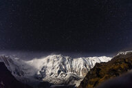 Scenic view of snowcapped mountains against star field at night - CAVF62785