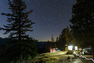 Illuminated cottage amidst trees against star trails in forest at night - CAVF62794