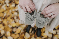 High angle view of pregnant woman holding baby booties while standing in forest during autumn - CAVF62809
