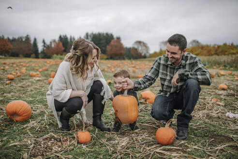 Happy family enjoying on pumpkin patch during autumn - CAVF62815