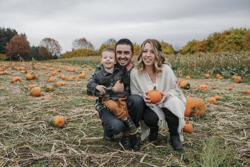 Portrait of happy family crouching on pumpkin patch during autumn - CAVF62818