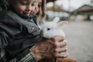 Close-up of cute smiling son playing with rabbit by parents at farm - CAVF62827