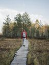 Rear view of man with backpack walking on boardwalk amidst grassy field against sky in forest - CAVF62842
