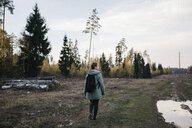 Rear view of woman with backpack walking on grassy field against sky in forest - CAVF62845