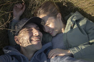 High angle close-up of happy couple lying on grassy field - CAVF62848