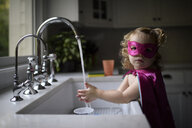 Portrait of girl wearing superhero costume washing hands in kitchen sink while standing at home - CAVF62872