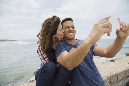Affectionate couple taking selfie with camera phone ocean - HEROF27704