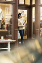 Mature woman standing in door of a fashion store, holding laptop - PESF01517