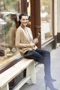 Mature woman sitting in front of her fashion store, using tablet - PESF01520