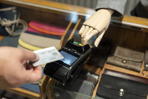 Customer paying with creditcard, robot assisting - PESF01526