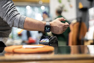 Customer paying contactless with his smartwatch - PESF01529