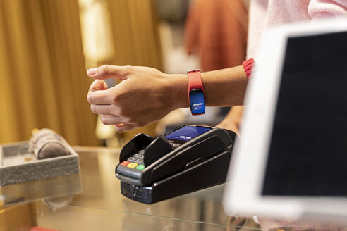 Customer paying contactless with her smartwatch - PESF01538