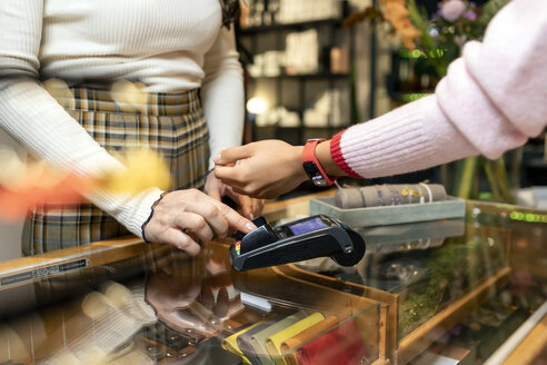 Customer paying contactless with her smartwatch - PESF01544