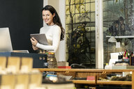 Mature woman working in fashion store, using digital tablet - PESF01547