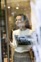 Mature woman standing in shop , smiling, with open sign hanging in window - PESF01553