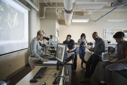 Science professor at microscope leading lesson in classroom - HEROF27736