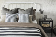 Striped and patterned pillows and blanket on bed - HEROF27757