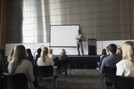 Professor on stage speaking to students in auditorium - HEROF27787