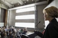 Professor speaking at podium to auditorium audience - HEROF27808