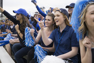 Smiling fans in blue pointing bleachers sports event - HEROF27811