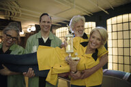 Teammates holding woman with trophy in bowling alley - HEROF27820