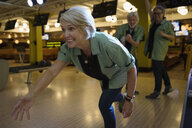 Woman bowling with team at bowling alley - HEROF27823