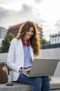Young businesswoman sitting on stairs in the city, working with laptop - GIOF05777