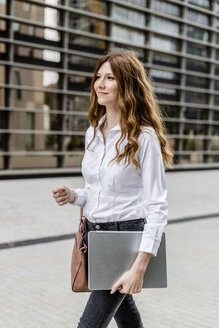 Young businesswoman walking in the city, carrying laptop - GIOF05828