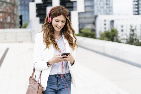 Young businesswoman commuting in the city, using smartphone and headphones - GIOF05849