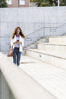 Young businesswoman commuting in the city, using smartphone - GIOF05855