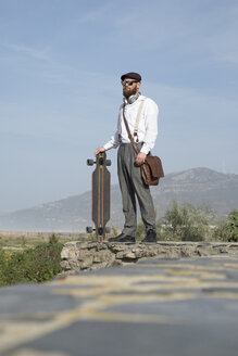 Bearded man standing on a wall with laptop, longboard and leather bag - KBF00587