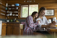 Affectionate young couple at cabin kitchen table - HEROF27837